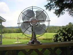 Ancien ventilateur posé sur un balcon. Source : http://data.abuledu.org/URI/53619bd8-ancien-ventilateur-pose-sur-un-balcon