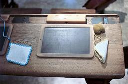 Ardoise sur un ancien bureau. Source : http://data.abuledu.org/URI/501dc5c8-ardoise-sur-un-ancien-bureau