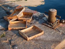 Cinq cagettes en bois vides sur le quai. Source : http://data.abuledu.org/URI/538998dc-cinq-cagettes-en-bois-vides-sur-le-quai