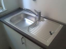 Évier neuf en inox avec robinet. Source : http://data.abuledu.org/URI/535c20df-evier-neuf-en-inox-avec-robinet