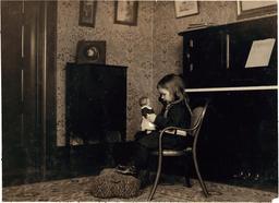 Fillette jouant à la poupée en 1912. Source : http://data.abuledu.org/URI/52629938-fillette-jouant-a-la-poupee-en-1912