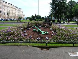Horloge sur un parterre fleuri. Source : http://data.abuledu.org/URI/529a6dd4-horloge-sur-un-parterre-fleuri