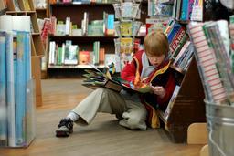Jeune lecteur assis dans une librairie. Source : http://data.abuledu.org/URI/5962b265-jeune-lecteur-assis-dans-une-librairie