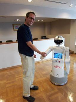 Le robot ENON serrant la main d'un client. Source : http://data.abuledu.org/URI/529b1cd5-le-robot-enon-serrant-la-main-d-un-client