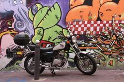 Moto Honda devant un mur taggé de Marseille. Source : http://data.abuledu.org/URI/528893c3-moto-honda-devant-un-mur-tagge-de-marseille