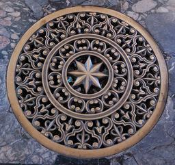 Plaque d'égout sur sol de marbre. Source : http://data.abuledu.org/URI/534fa49a-plaque-d-egout-sur-sol-de-marbre