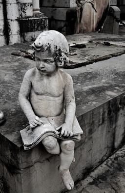 Statue de petit lecteur assis dans un cimetière. Source : http://data.abuledu.org/URI/5962bff8-statue-de-petit-lecteur-assis-dans-un-cimetiere