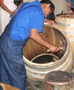 Travail à l'herminette d'un tonneau. Source : http://data.abuledu.org/URI/51dbdb00-travail-a-l-herminette-d-un-tonneau