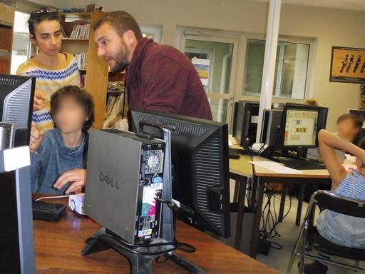 Laurent et Christine aident un collégien à programmer Thymio