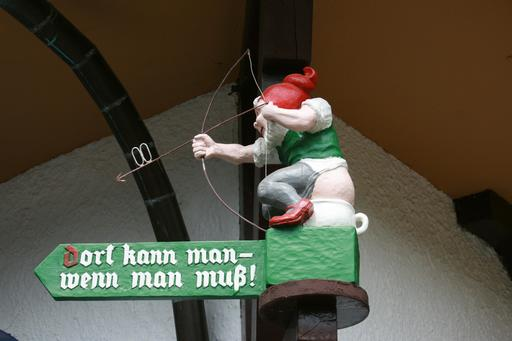 Panneau du nain tireur sur son pot de chambre