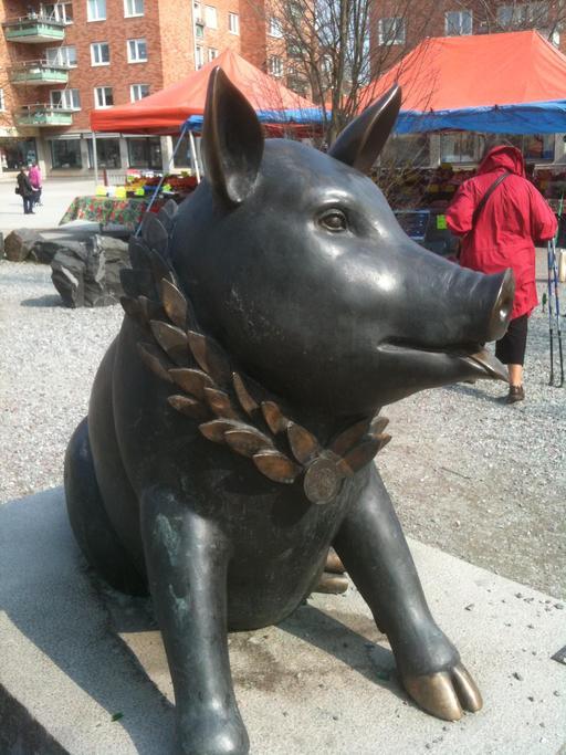 Statue de cochon avec une couronne de lauriers