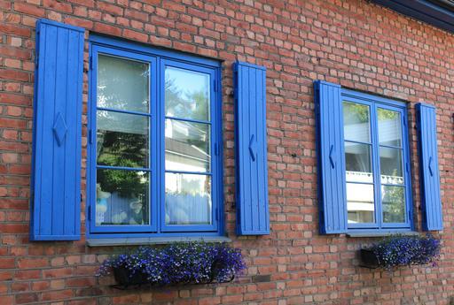 Volets bleus sur une façade en brique
